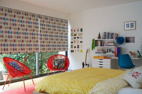 Multicolour patterned roller blind hung in a teenager's bedroom