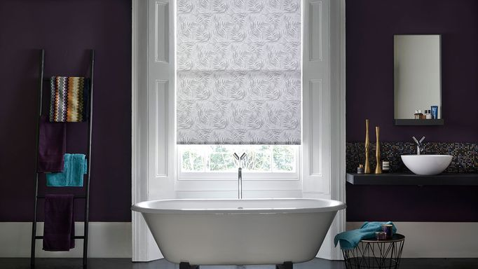Modern bathroom with dark plum walls and sash windows dressed with grey pattern roller blind