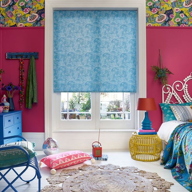 Colourful bohemian bedroom with hot pink walls and blue furniture with a blue pattern roller blind