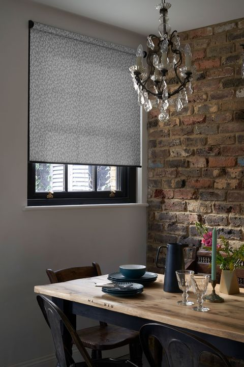 Rustic dining room with exposed brick wall and a grey pattern roller blind