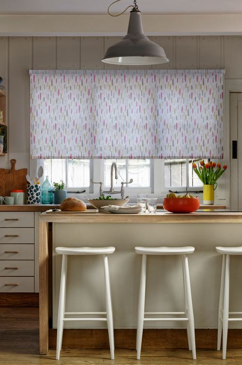 Country kitchen with wooden panels and pink patterned roller blinds