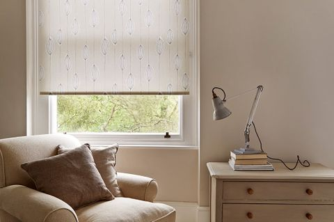 A beige living room featuring a window with a neutral coloured, leaf patterned roller blind in the window.