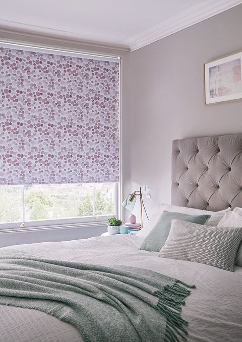 Feminine chic bedroom with double bed with soft pastel colour throws and cushions and roller blinds in a pink pattern fabric