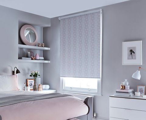 Feminine chic bedroom with minimalist decor and pink patterned roller blinds in blush