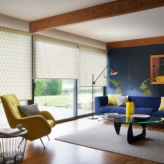 Modern living room with retro style decor and wide windows dressed with retro yellow floral roller blinds
