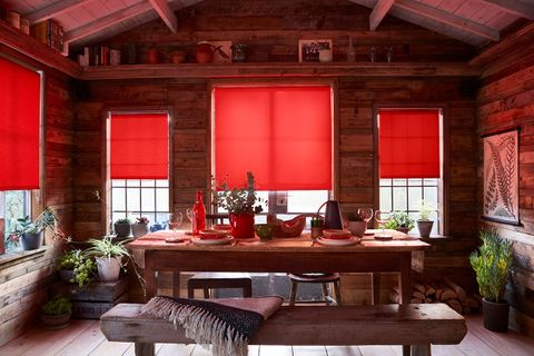 Red blinds in a cosy wooden kitchen featuring a table