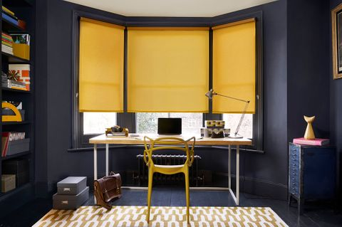 Home office with dark walls and colourful mustard roller blinds