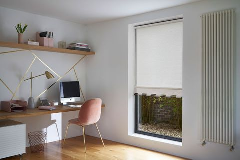 Modern home office with a full length window dressed with a white roller blind