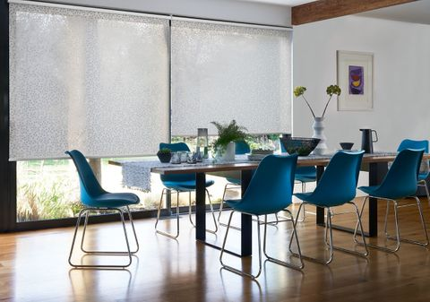 Modern dining room with colourful blue chairs and large windows dressed with white patterned roller blinds
