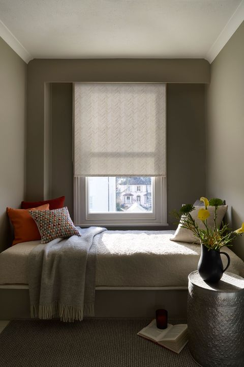 A neutral coloured patterned roller blind hangs in a window behind a bed
