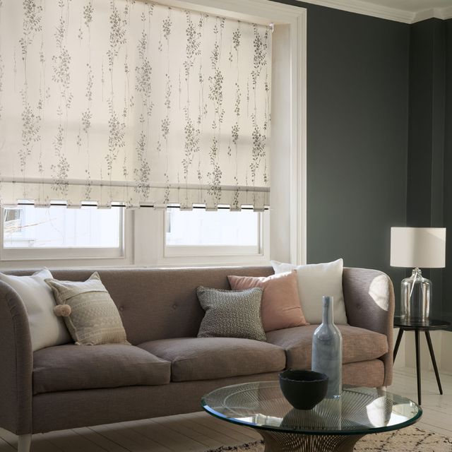 Modern Chic Living room with minimalist decor and a window dressed with a white pattern roller blind