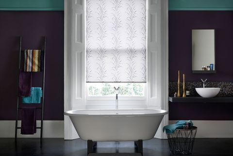 Modern bathroom with dark purple walls and a patterned white roller blind