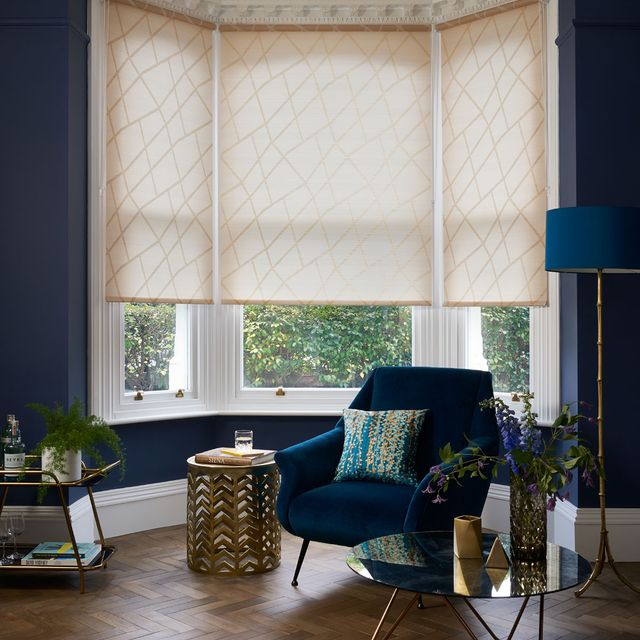 Modern luxe living room with a bay window dressed with gold pattern Roller Blind