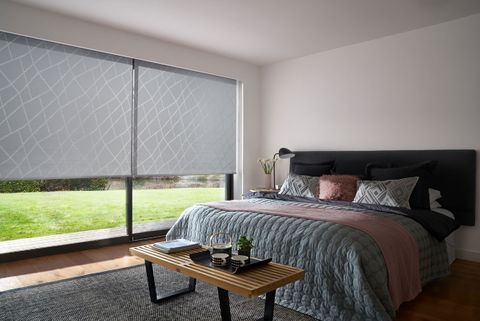 A Grey Patterned Roller Blind in Silver in a one bed Bedroom