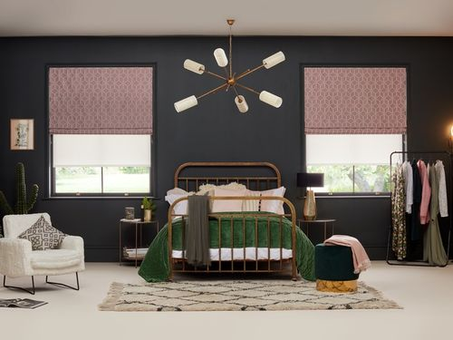 A bedroom which is decorated with navy blue walls and pink roller blinds in a repeating geometric pattern which are fitted to rectangular windows either side of the bed