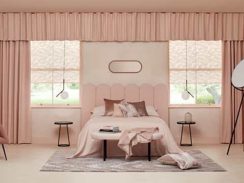 A pink bedroom with pink soft furnishings