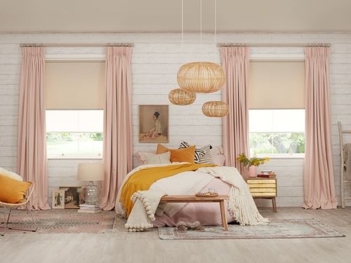 A white brick bedroom is decorated with pink curtains matched with cream coloured roller blinds that have been fitted to rectangular windows