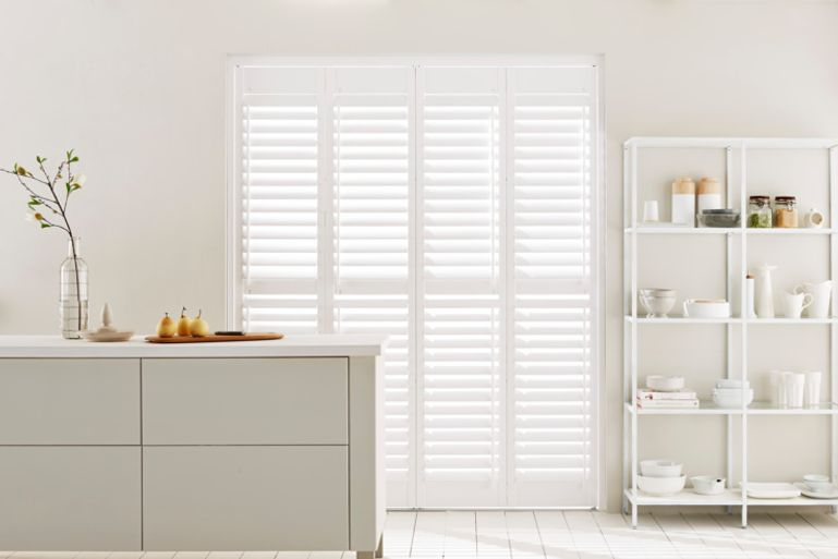 modern white decor kitchen with white full height tracked shutters in the window