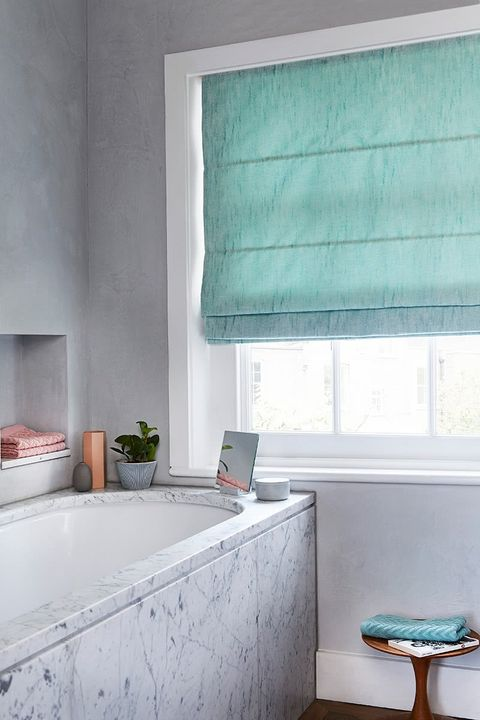 Bathroom with marble effect and light blue roman blind