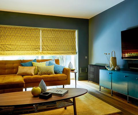 Retro style living room with blue and yellow decor and large windows dressed with yellow Roman blinds