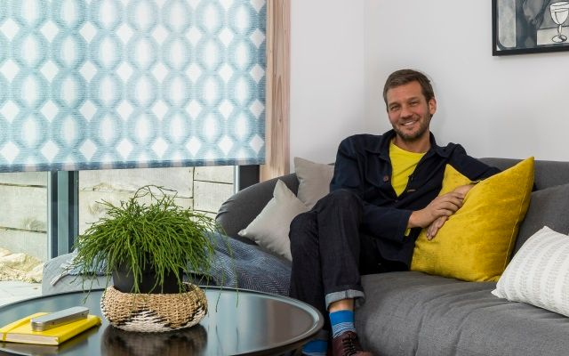 charlie luxton sitting in his living room beside a geometric printed blue roller blind