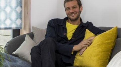 Charlie Luxton sat on a gray couch with yellow cushions