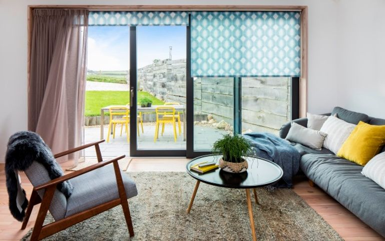 charlie luxton's living room with blue patterned roller blinds in a patio window