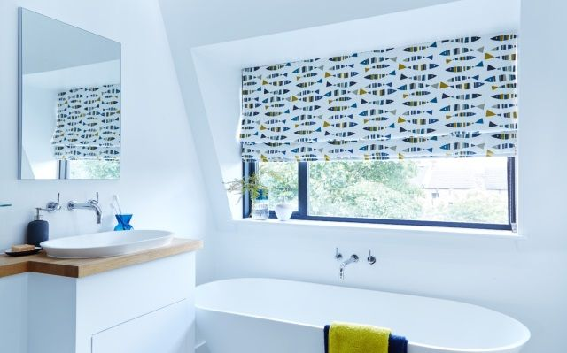 white decor bathroom with colourful fish patterned roman blinds in the window