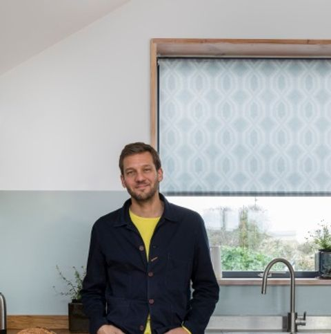 charlie luxton standing by the sink in his kitchen with a blue printed roller blind in the window