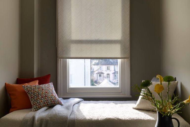 light brown roller blinds in a bedroom window
