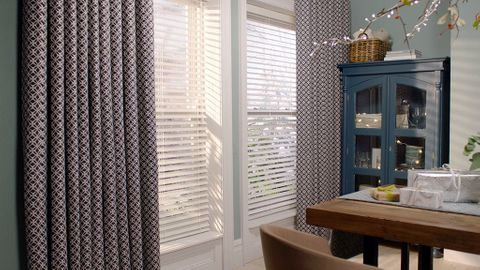 Festive dining area with a window dressed with white venetian blinds and luxurious print curtains