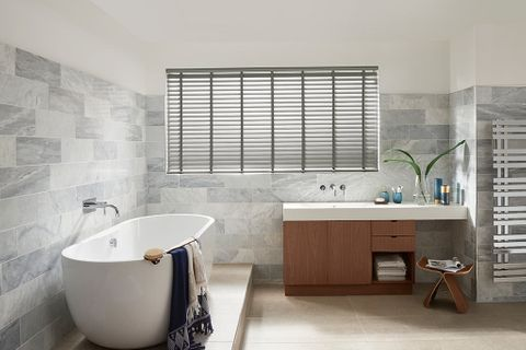 Modern luxe bathroom with white ceramic tub and grey venetian blinds