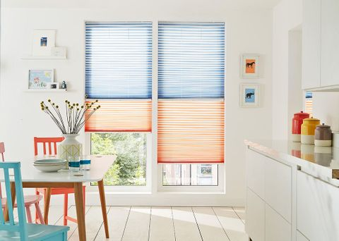 Colourful kitchen with pleated blinds in orange and blue fabric