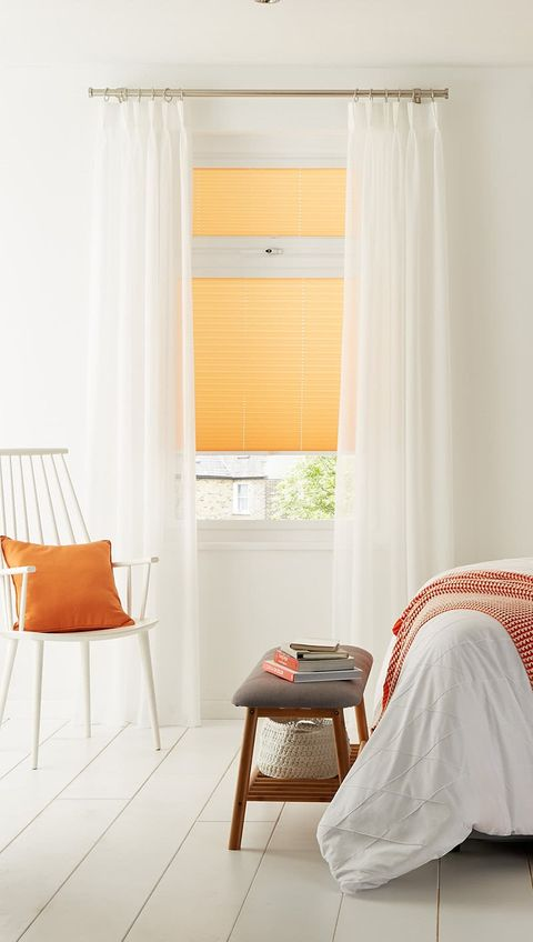 All-white decor bedroom with orange pleated blind