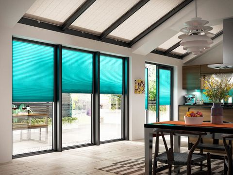 Modern open plan kitchen diner with large bifold doors dressed with blue turquoise pleated blinds