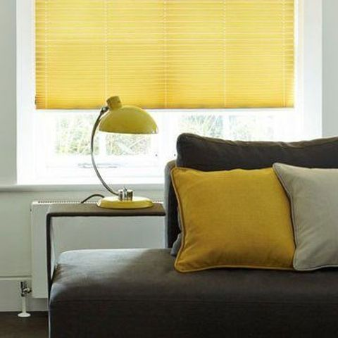 Close up of grey living room sofa with yellow pleated blinds in the background
