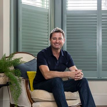 George clarke sat on a cream chair in a living room that has teal coloured shutters