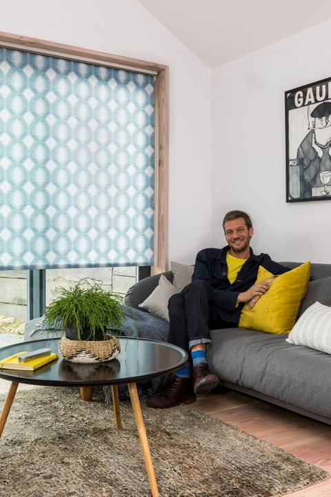 Charlie Luxton sat in a Living Room with blue roller blinds