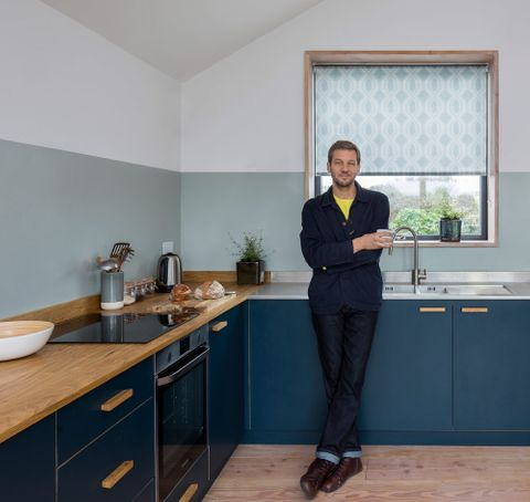Charlie Luxton in a kitchen with natural wood counters and with a window dressed with grey roller blind