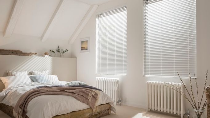 matt white venetian blinds in a bedroom window