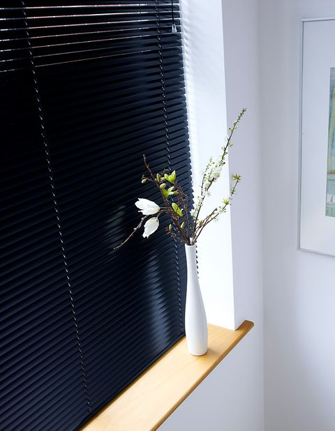 A close up of a black blind in a white room with a white vase
