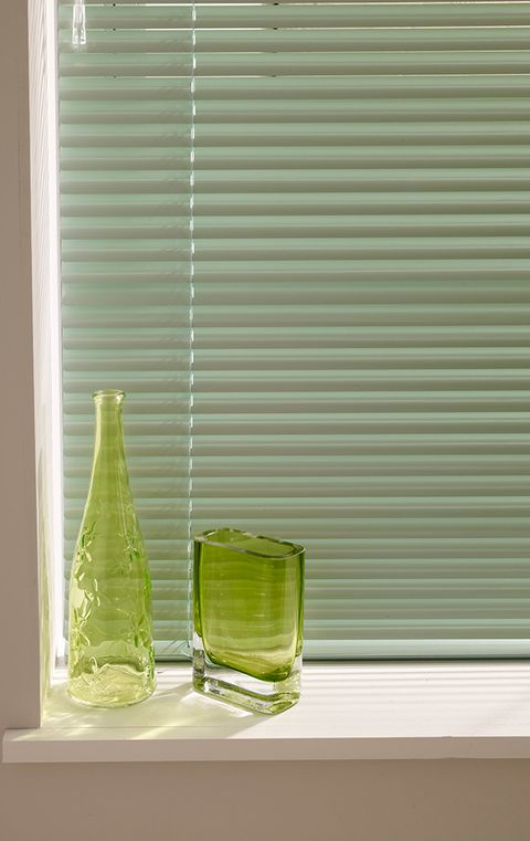 A close up of Venetian blinds in green