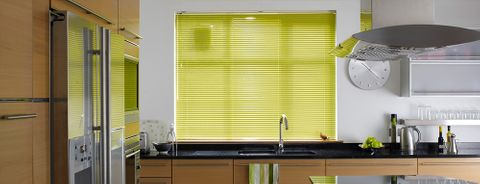 A bright green Venetian blind in a wooden kitchen