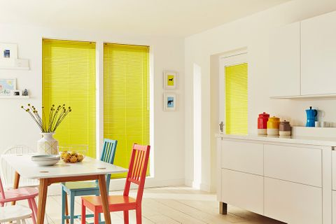 A cream kitchen featuring bright yellow Venetian blinds behind a table with a vase