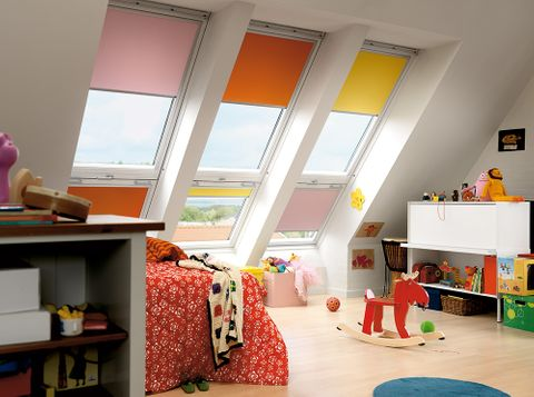 A child's bedroom featuring different coloured skylight blinds in pink, orange and yellow shades