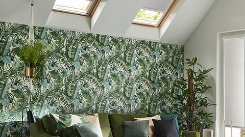 Skylight blinds in Acacia Silver are fitted to two skylight windows in a living room decorated in floral colours including the wallpaper, sofa and various plants