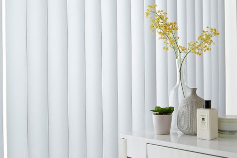 A close up of white vertical blinds in a window