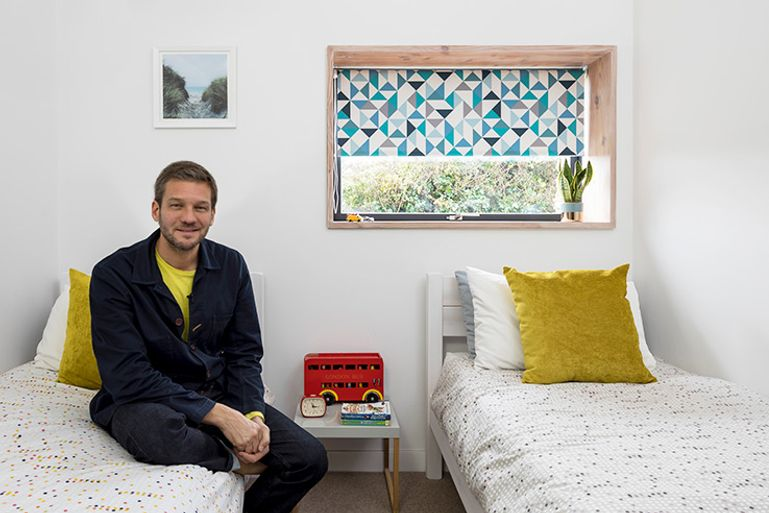 charlie luxton showing his children's bedroom with geometric print blue roller blinds in the window