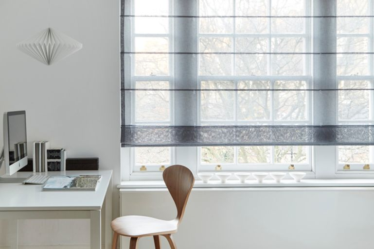 Modern study with wooden and white furnishings, with an opaque grey roman blind hug over the window in the fabric Astro Steel.