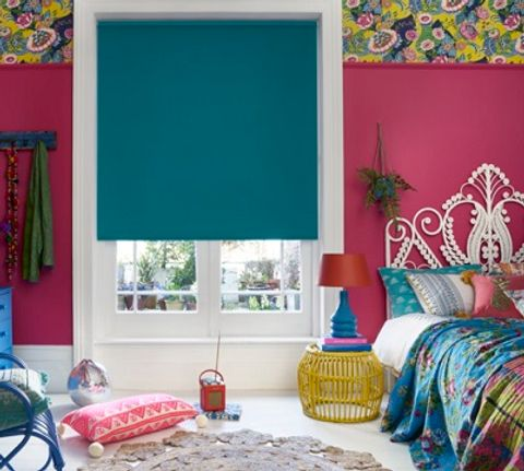 Large hot pink bedroom with a Cordova Peacock blue roller blind fitted to the window